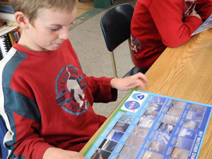 Boy in class looking at cloud chart  provided by NASA